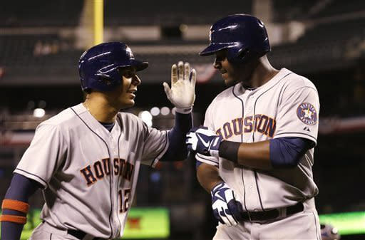 Houston Astros' Chris Carter, right, is congratulated by Carlos Pena on his home run against the Seattle Mariners in the seventh inning of a baseball game Wednesday, April 10, 2013, in Seattle. (AP Photo/Elaine Thompson)