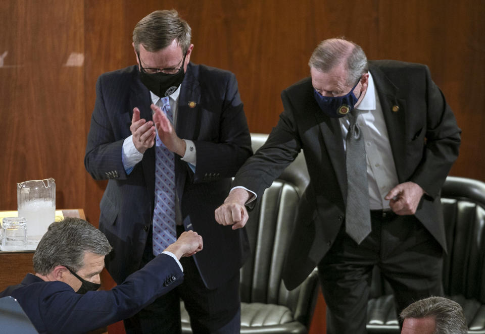 Sen. Phil Berger, right, fist bumps North Carolina Gov. Roy Cooper after Cooper delivered his State of the State address before a joint session of the North Carolina House and Senate, Monday, April 26, 2021, in Raleigh, N.C. (Robert Willett/The News & Observer via AP)