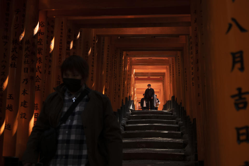 Tourists walk through torii gates at Fushimi Inari Shrine in Kyoto, Japan, March 18, 2020. Japanese tourism industry has taken a beating after Beijing banned group tours in late January. (AP Photo/Jae C. Hong)