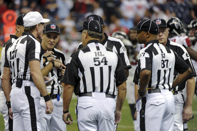 FILE - In this Dec. 4, 2011, file photo, officials confer in the fourth quarter of an NFL football game between the Atlanta Falcons and Houston Texans in Houston. The NFL and referees' union reached a tentative agreement on Wednesday, Sept. 26, 2012, to end a three-month lockout that triggered a wave of frustration and anger over replacement officials and threatened to disrupt the rest of the season. (AP Photo/Dave Einsel, File)
