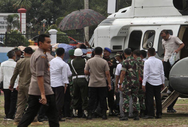 Soldiers carry Indonesian Coordinating Minister for Politics, Law and Security Wiranto on a stretcher to a waiting helicopter to be evacuated to Jakarta, in Pandeglang, Banten province, Indonesia, Thursday, Oct. 10, 2019. Indonesian police officials say Wiranto and two other people, including a local police chief, have been wounded by a knife-wielding man and taken to a hospital during a visit to a western province. (AP Photo/Rafsanjani)