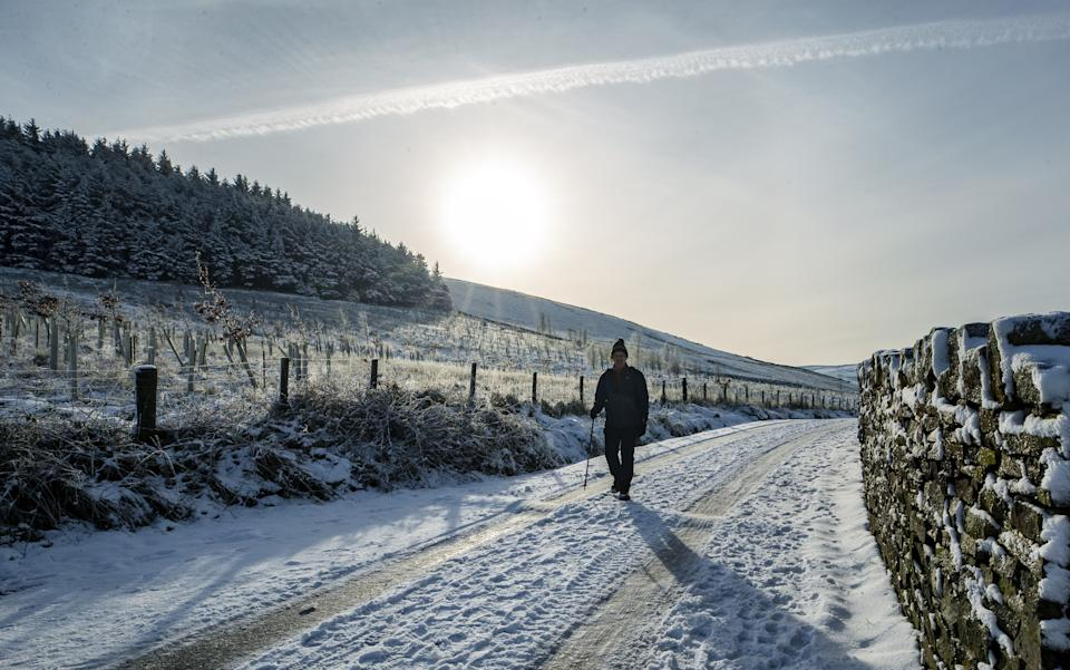 A person walks through the snow at Blackmoss Reservoir in Barley, Pendle, Lancashire. Weather and travel warnings remain in place for icy conditions across much of England and Scotland after the widespread snowfall of recent days. (Photo by Peter Byrne/PA Images via Getty Images)