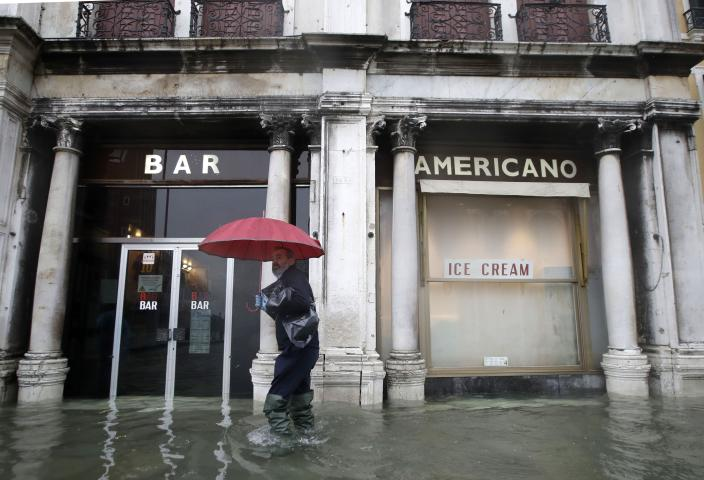 A man walks past a closed cafe in a flooded Venice, Italy, Tuesday, Nov. 12, 2019. (Photo: Luca Bruno/AP)
