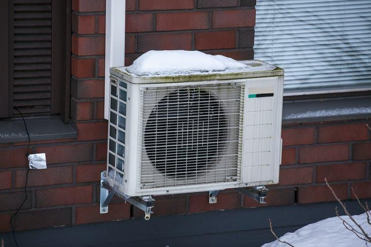 A square unit resembling an air conditioner mounted on an external brick wall.