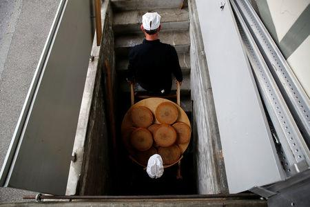 "Cheese makers carry the nine wheels of cheese for a tasting in the K3 cellar after the experiment to ""insonify"" cheese with different types of music by the University of the Arts in Burgdorf"