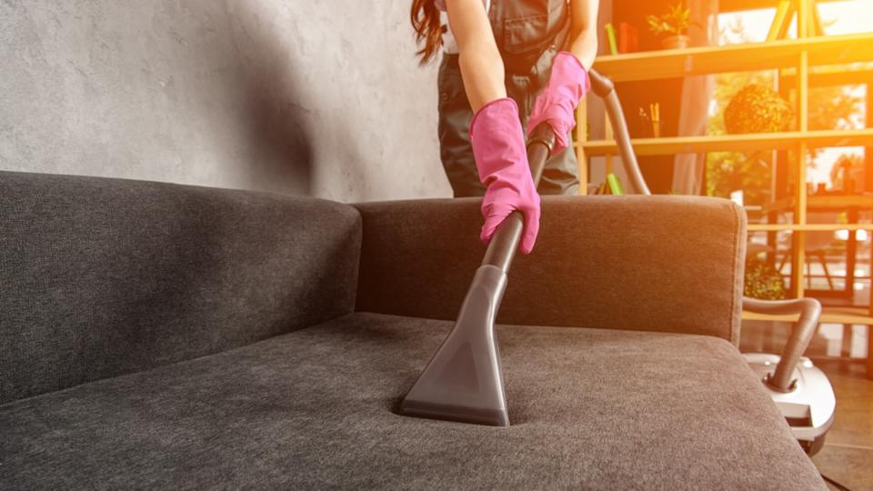 cropped shot of woman in rubber gloves cleaning sofa with vacuum cleaner