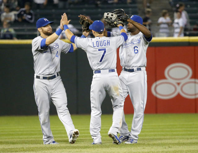 Kansas City Royals right fielder David Lough (7), Alex Gordon, left, and Lorenzo Cain celebrate a 5-1 win over the Chicago White Sox after a baseball game on Friday, July 26, 2013, in Chicago. (AP Photo/Charles Rex Arbogast)