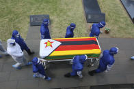 Pallbearers carry the coffin of a top government official at the National Heroes Acre in Harare, Wednesday, Jan, 27, 2021. Zimbabwe on Wednesday buried three top officials who succumbed to COVID-19, in a single ceremony at a shrine reserved almost exclusively for the ruling elite as a virulent second wave of the coronavirus takes a devastating toll on the country. (AP Photo/Tsvangirayi Mukwazhi)