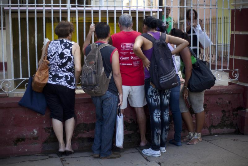 People read adjustments to the migratory policy, posted on a wrought iron fence of an immigration office in Havana, Cuba, Tuesday, Oct 16, 2012. The Cuban government announced Tuesday that it will no longer require islanders to apply for an exit visa, eliminating a much-loathed bureaucratic procedure that has been a major impediment for many seeking to travel overseas for more than a half-century. (AP Photo/Ramon Espinosa)