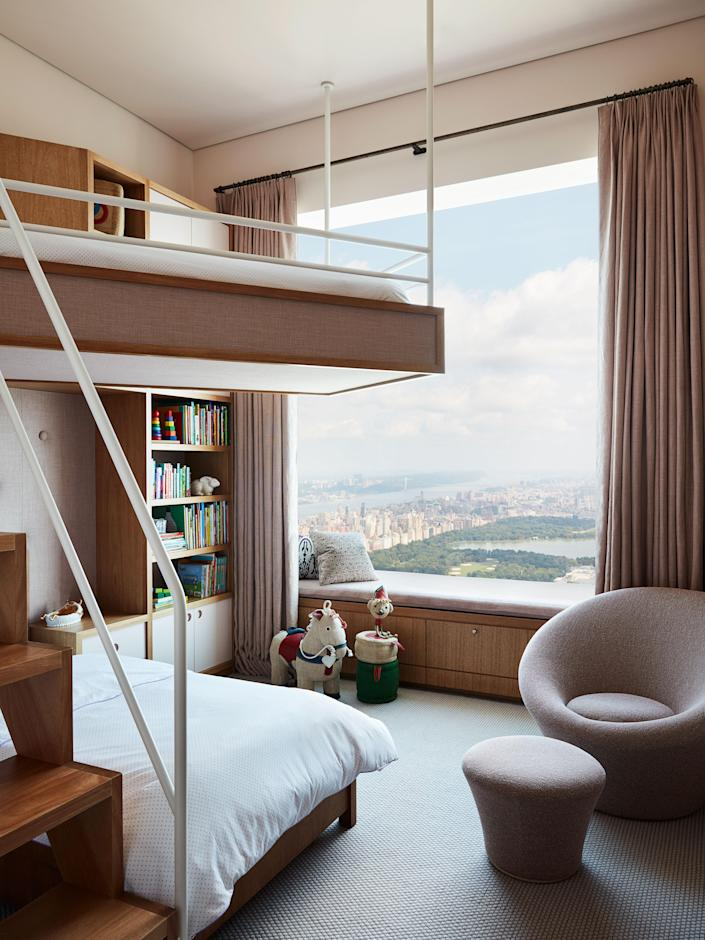 A child's bedroom has a custom bleached-mahogany bunk bed with D. Porthault linens, a Pierre Paulin chair covered in Maharam fabric, wool carpet by Stark, and curtains in a Kerry Joyce linen.