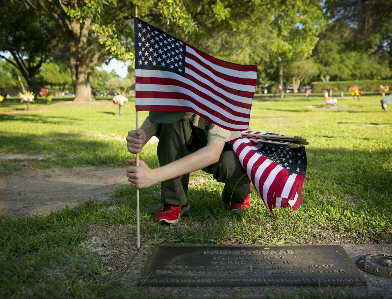 <p>Nathan Thom, 12, of BSA Troop 8787, places a U.S. flag on the grave of a veteran at the Cook-Walden Capital Parks Cemetery in Pflugerville, Texas, on Saturday May 26, 2018. For nearly 20 years, the scouts in the troop, which is chartered with VFW Post 8787, have gathered on the Saturday before Memorial Day to place about 5,000 flags on graves to honor veterans. (Photo: Jay Janner/Austin American-Statesman via AP) </p>