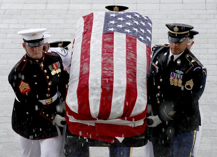 A military honor guard team carries the casket of the late senator into the Capitol. (Photo: Win McNamee/Getty Images)