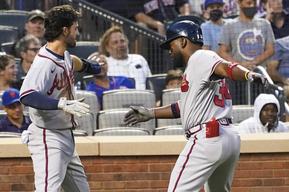 Atlanta Braves' Abraham Almonte, right, and Dansby Swanson celebrate after scoring on Almontes' two-run home run during the third inning of the team's baseball game against the New York Mets, Tuesday, July 27, 2021, in New York. (AP Photo/Mary Altaffer)
