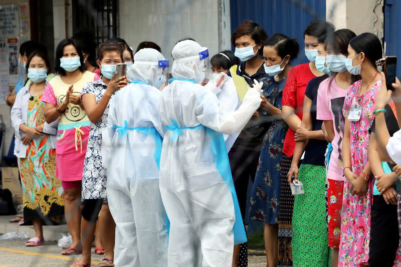 FILE PHOTO: Top Glove workers wait in line to be tested for the coronavirus disease (COVID-19) outside a hostel under enhanced lockdown in Klang