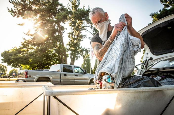 "Edward ""Ed"" Ulbricht, 61, dumps cans and bottles into one of the Springfield BottleDrop's carts shortly before closing. Oregon's can and bottle redemption program has seen a significant increase in participation and return since the pandemic started. [Dana Sparks/The Register-Guard] - registerguard.com"