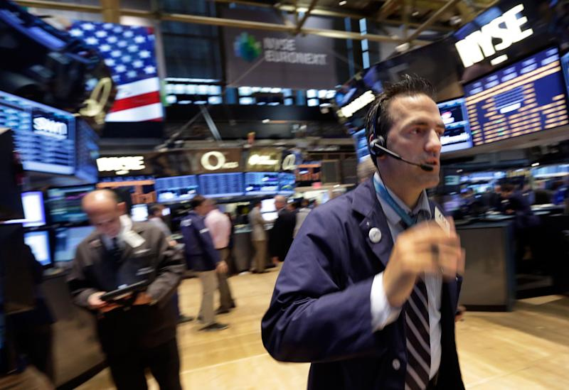 In this Friday, Aug. 16, 2013 photo, trader Gregory Rowe, right, works on the floor of the New York Stock Exchange. Worries about a potential military strike against Syria are dragging down the stock market in early trading, Tuesday, Aug. 27, 2013. (AP Photo/Richard Drew)