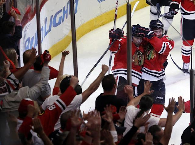 Chicago Blackhawks left wing Patrick Sharp, left, celebrates his goal with right wing Ben Smith during the first period in Game 7 of the Western Conference finals in the NHL hockey Stanley Cup playoffs Sunday, June 1, 2014, in Chicago. (AP Photo/Charles Rex Arbogast)