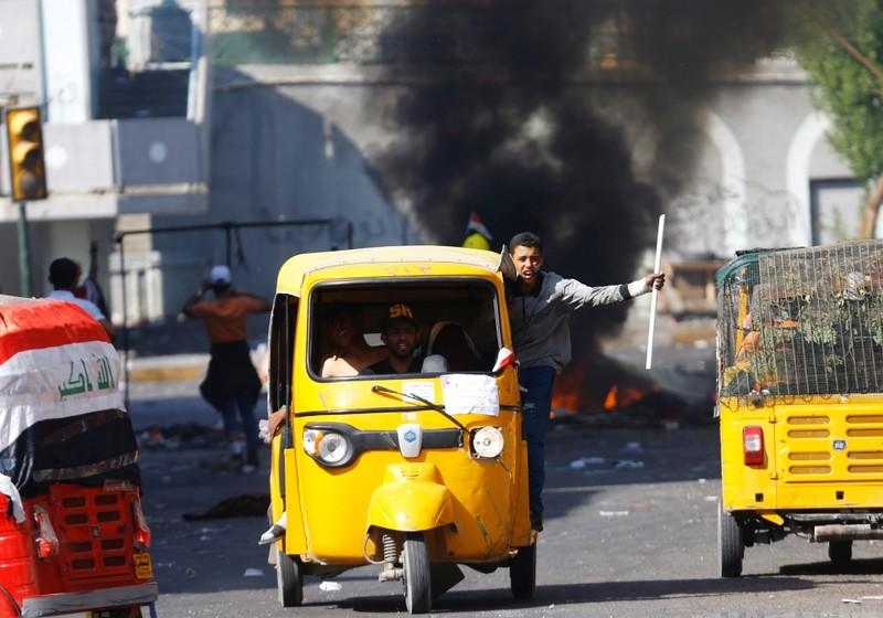 Demonstrators use tuk-tuk during the ongoing anti-government protests in Baghdad