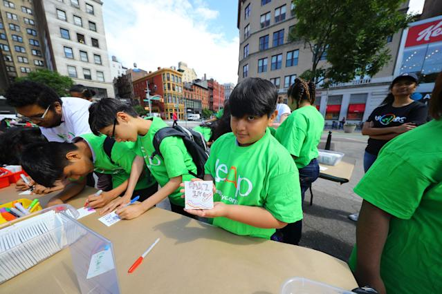 <p>A student from I.S. 117 Joseph H. Wade in the Bronx holds up an art board he created, in Union Square Park in New York City on June 5, 2018. (Photo: Gordon Donovan/Yahoo News) </p>