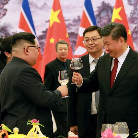 President Xi Jinping (R) and North Korean leader Kim Jong Un (L) raising their glasses at the Great Hall of the People in Beijing - Credit: KCNA/AFP