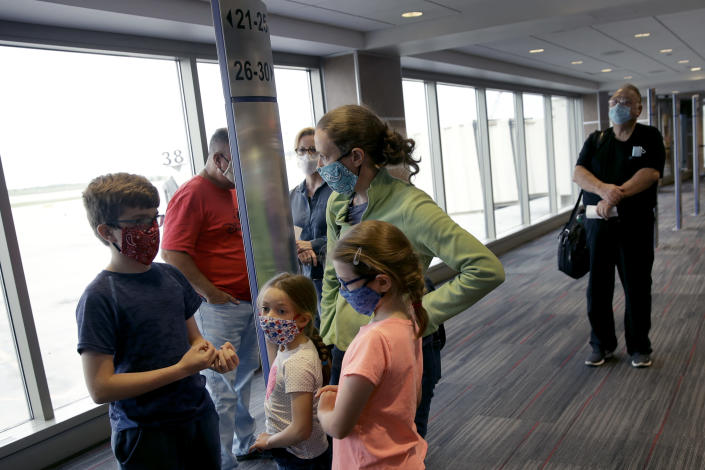 FILE - People wearing masks wait to board a Southwest Airlines flight at Kansas City International airport in Kansas City, Mo., in this May 24, 2020, file photo. Governments and businesses are scrambling to change course following new federal guidance calling for the return of mask wearing in virus hot spots amid a dramatic spike in COVID-19 cases and hospitalizations nationwide. Nevada and Kansas City were among the locations that moved swiftly to re-impose indoor mask mandates following Tuesday's, July 27, 2021, announcement from the Centers for Disease Control and Prevention. (AP Photo/Charlie Riedel, File)