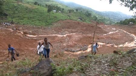 People walk up the mudslide in the mountain town of Regent, Sierra Leone in this still image taken from a video. via Reuters TV