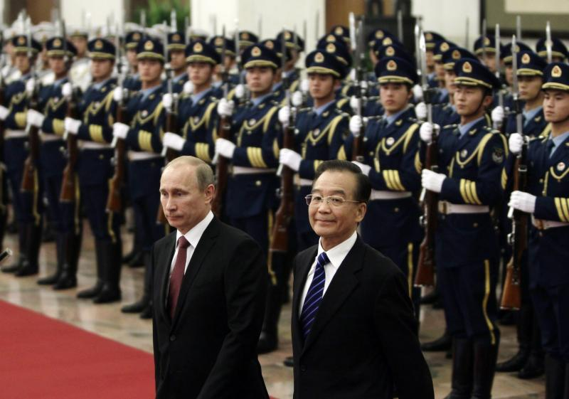 Russian Prime Minister Vladimir Putin, left, and Chinese Premier Wen Jiabao, right, inspect a guard of honor during a welcoming ceremony at the Great Hall of the People in Beijing, China on Tuesday, Oct. 11, 2011. (AP Photo/Jason Lee, Pool)