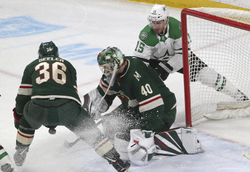 Minnesota Wild goalie Devan Dubnyk, center, stops a shot as Dallas Stars' Blake Comeau, right, looks for a rebound in the first period of an NHL hockey game Thursday, March 14, 2019, in St. Paul, Minn. (AP Photo/Jim Mone)