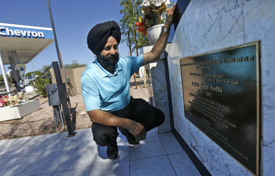"""FILE - In this Aug. 19, 2016 file photo, Rana Singh Sodhi, kneels near his service station in Mesa, Ariz., next to a memorial for his brother, Balbir Singh Sodhi, who was murdered in the days after the Sept. 11 terrorist attacks. Sodhi, a Sikh American was killed at his Arizona gas station four days following the Sept. 11 attacks by a man who announced he was """"going to go out and shoot some towel-heads"""" and mistook him for an Arab Muslim. (AP Photo/Ross D. Franklin, File)"""