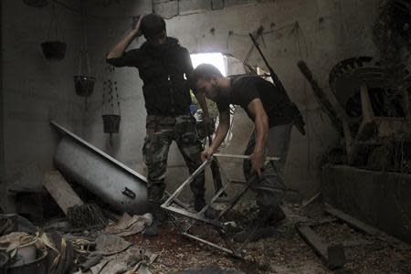 Free Syrian Army fighters inspect damaged items in a house in Aleppo