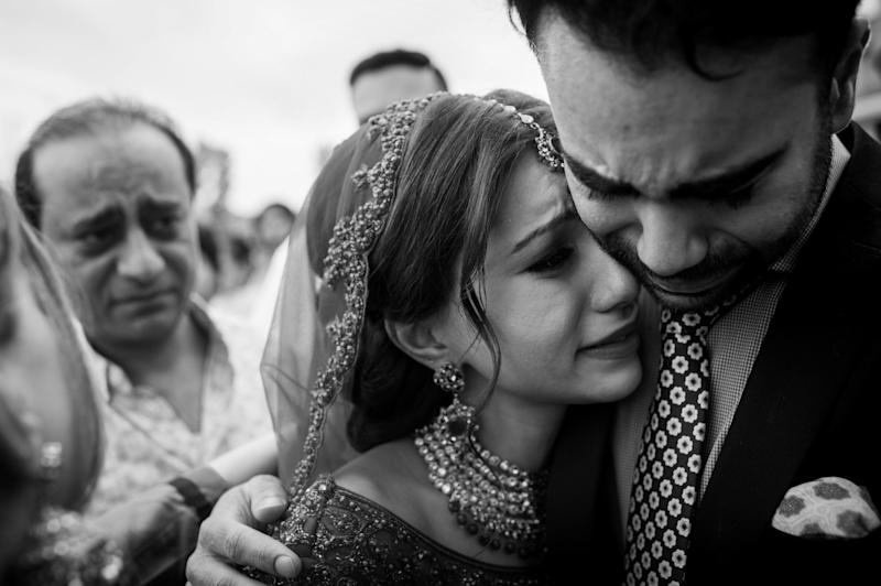 """Vinita hugging her brother (with her father in the background) after her wedding ceremony. It's a traditional part of the Sikh ceremony where the bride's family does a farewell called the 'doli'."" -- <i>Gurminder Banga</i>"