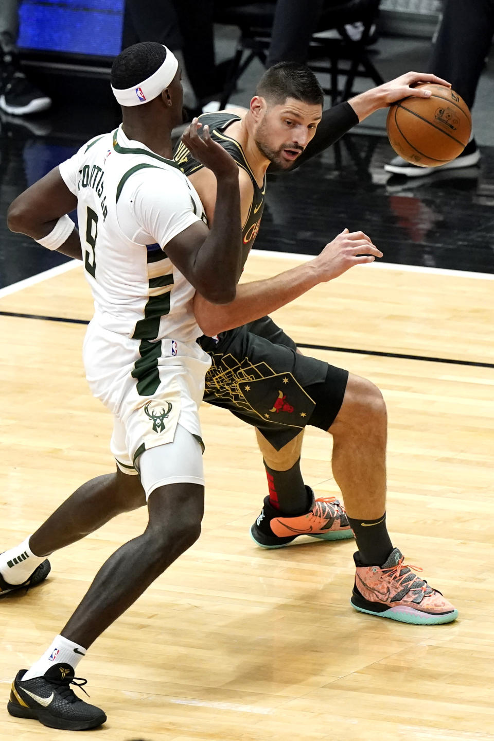 Chicago Bulls center Nikola Vucevic, right, drives against Milwaukee Bucks center Bobby Portis during the first half of an NBA basketball game in Chicago, Friday, April 30, 2021. (AP Photo/Nam Y. Huh)