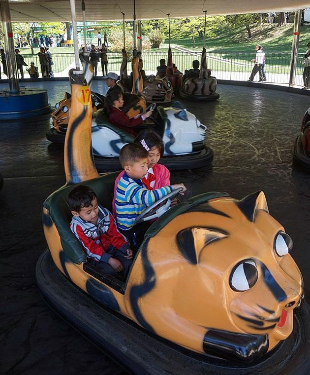 Locals enjoy the bumper cars at Taesongsan Park in North Korea. Photo: Caters News