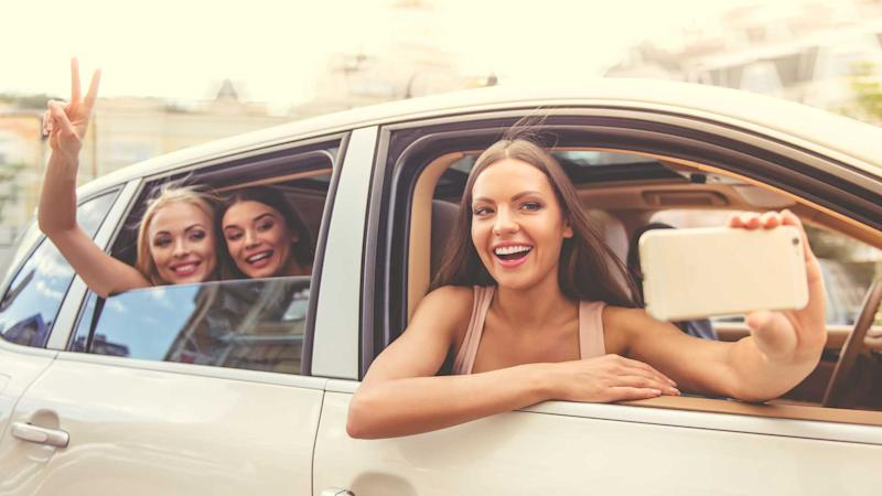 Young women taking selfies with phone while leaning out car window