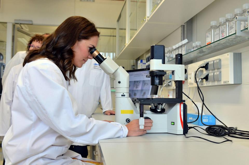 <p><b><b><b>The Duchess looks into a microscope during her visit to the German Cancer Research Institute in Heidelberg, Germany.<br><em>[Photo: PA]</em> </b></b></b></p>