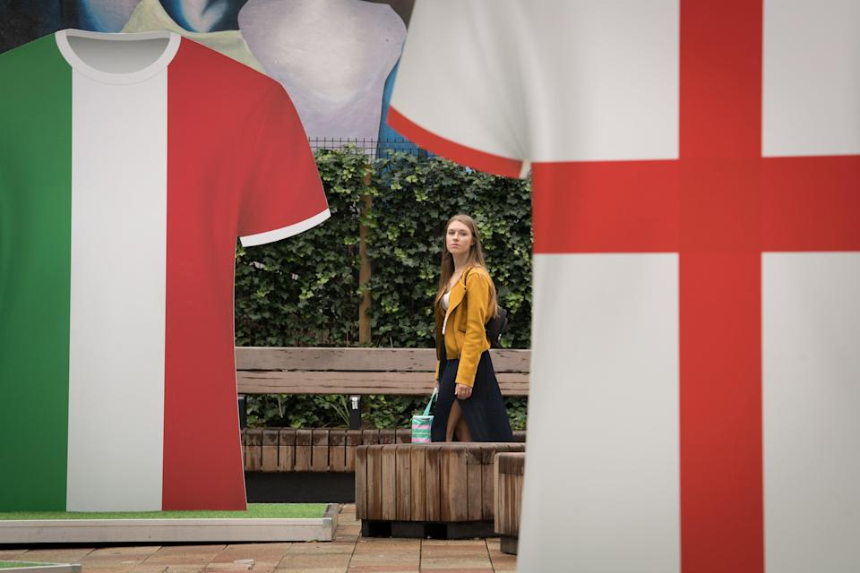 A woman walks past Italy and England football shirts (PA Wire)