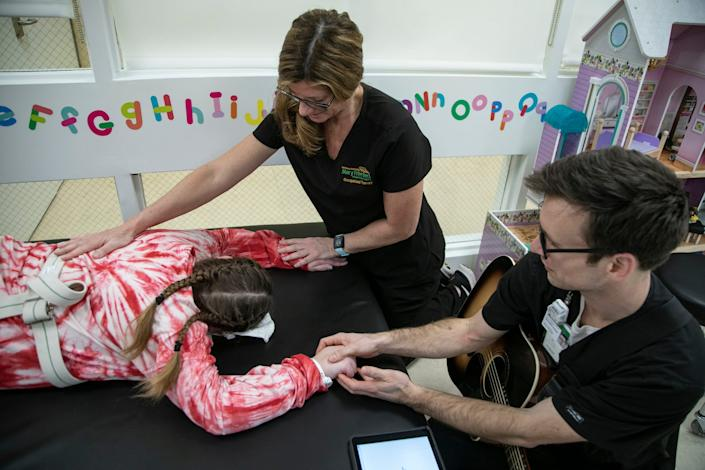Occupational therapists Jennifer Ancans and music therapist Peter Muszkiewicz stretch Savanah DeHart, 15, as she works through her rehabilitation at the Mary Free Bed Rehabilitation Hospital and Rapids Thursday, Jan. 23, 2020 to treat the debilitating effects of the Triple E (Eastern Equine Encephalitis) virus. DeHart was likely bitten by a an infected mosquito last summer and suffered stroke-like symptoms.