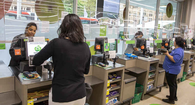 Woolworths shoppers standing in front of checkouts that have plexiglass screens installed to protect staff.