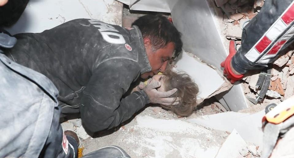Rescuer with toddler before pulling her from rubble after Turkey earthquake.
