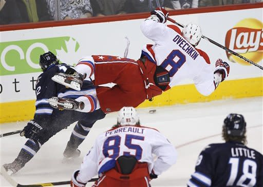 Washington Capitals' Alex Ovechkin (8) is checked by Winnipeg Jets' Randy Jones (12) during the first period of an NHL hockey game in Winnipeg, Manitoba, on Friday, March 16, 2012. (AP Photo/The Canadian Press, John Woods)