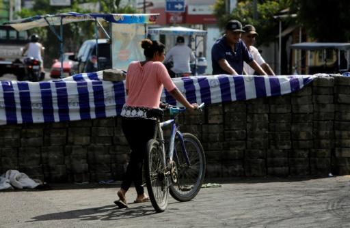 A woman passes next to a barricade in the city of Sebaco