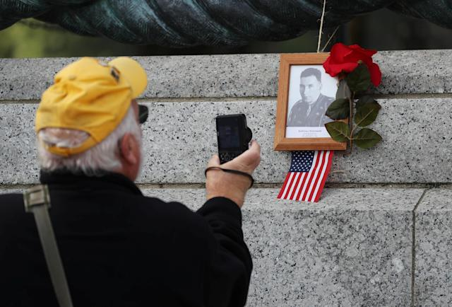 A man take a pitcures of an U.S. flag and a rose left by the portrait of a loved one at a Veterans Day Observance to honor the men and women who served in World War II in Washington, Nov. 11, 2019. (Photo: Siphiwe Sibeko/Reuters)