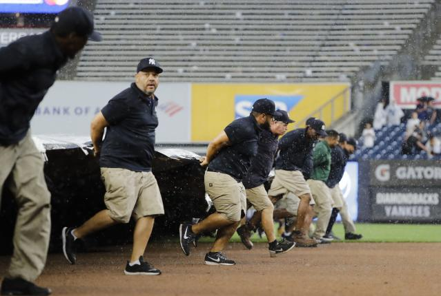 Grounds crew at Yankee Stadium cover the field during a rain delay during the sixth inning of a baseball game between the New York Yankees and the Arizona Diamondbacks Wednesday, July 31, 2019, in New York. (AP Photo/Frank Franklin II)