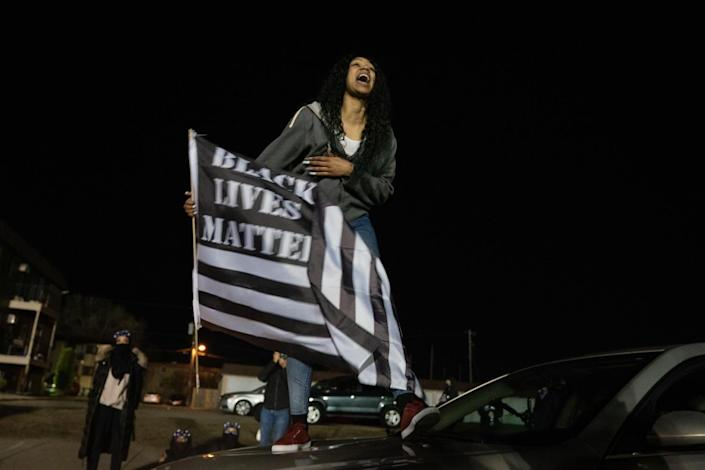 A protester stands on the hood of her car holding a Black Lives Matter flag outside the Brooklyn Center Police Department