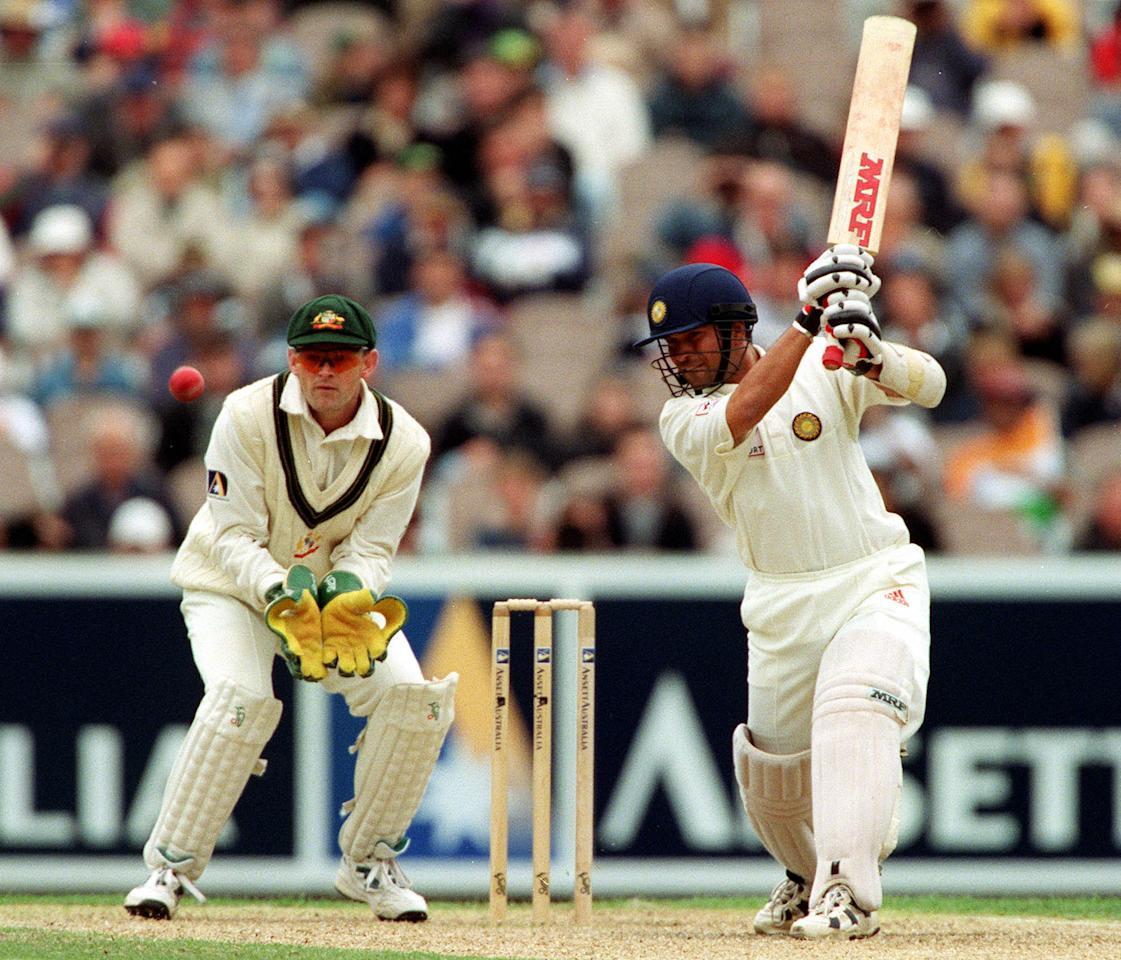 28  Dec 1999:  Sachin Tendulkar of India hits out on his way to 116 with Adam Gilchrist of Australia looking on, on day three of the second test match between Australia and India, played at the Melbourne Cricket Ground, Melbourne, Australia. India finished the day at nine for 235 runs. Mandatory Credit: Hamish Blair/ALLSPORT