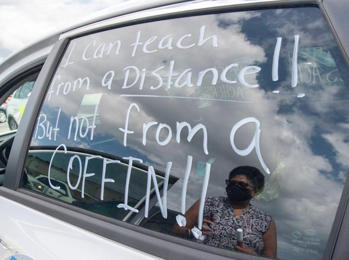 "Marie Foster, a reading teacher at Workman Middle School, is reflected along with a message on her car before fellow educators and parents begin their ""Car Parade for the Safe Reopening of Schools"" in Pensacola on Thursday, July 16, 2020. While they are eager to get back to the classrooms, they are calling for safe conditions before doing so."