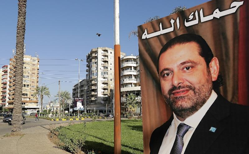 """A poster of Lebanese Prime Minister Saad Hariri, who resigned last week in a televised speech airing from the Saudi capital Riyadh, hangs on the side of a roundabout in Tripoli, Lebanon with a caption above reading in Arabic: """"God protect you"""""""