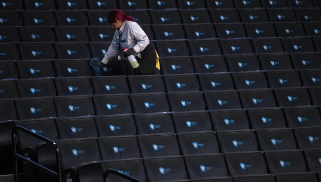 A worker disinfects seats prior to the start of the second round of the 2020 Atlantic 10 men's basketball tournament at Barclays Center on March 12, 2020 in the Brooklyn borough of New York City. The tournament was canceled amid growing concerns of the spread of Coronavirus (COVID-19). (Photo by Mike Lawrie/Getty Images)