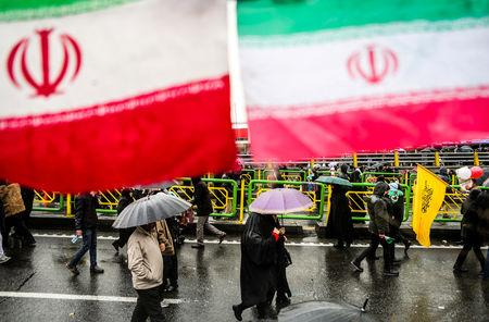Iranian people carry umbrellas during a ceremony to mark the 40th anniversary of the Islamic Revolution in Tehran, Iran February 11, 2019. Vahid Ahmadi/Tasnim News Agency/via REUTERS