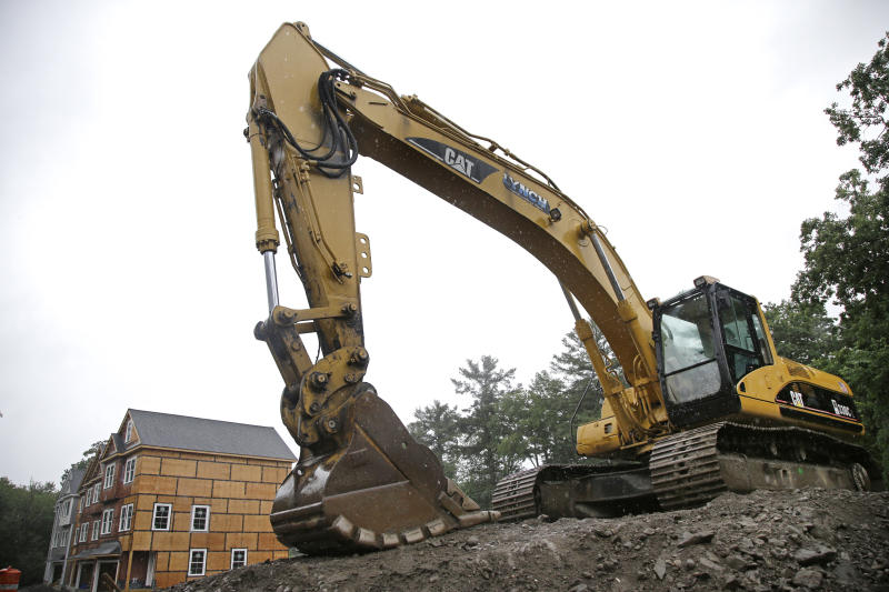 FILE- In this July 24, 2017, file photo, a Caterpillar excavator is on a housing construction site in North Andover, Mass. Caterpillar Inc. reports earnings Tuesday, Oct. 23, 2018. (AP Photo/Elise Amendola, File)